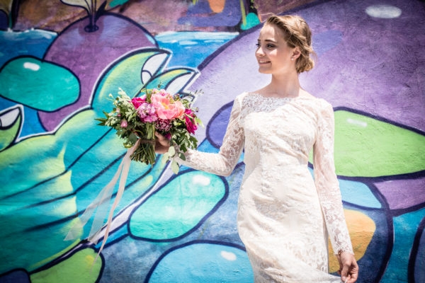 A photo of a bride with a bouquet in front of a colourful wall. In partnership with The Walper Hotel.