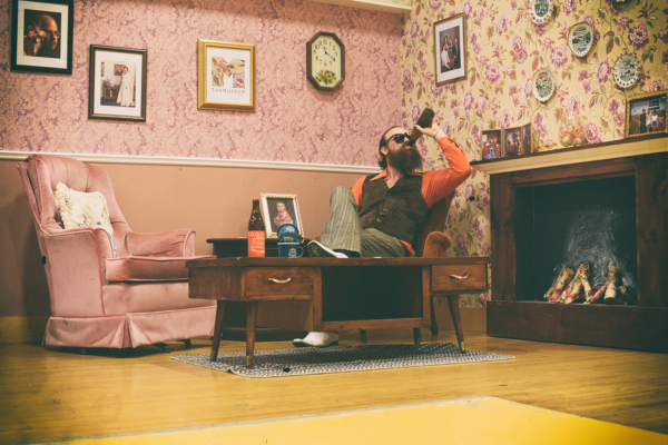 A photo of the replicated family rec room in partnership with TOQUE. A male is drinking a beer in the corner of a 70's themed room.