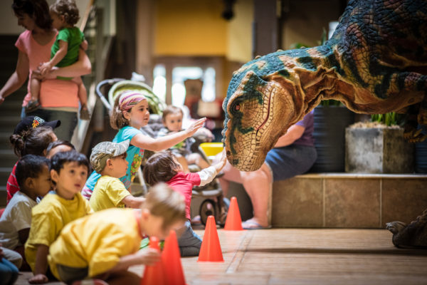A photo of Maverick the dinosaur with children visiting THEMUSEUM.