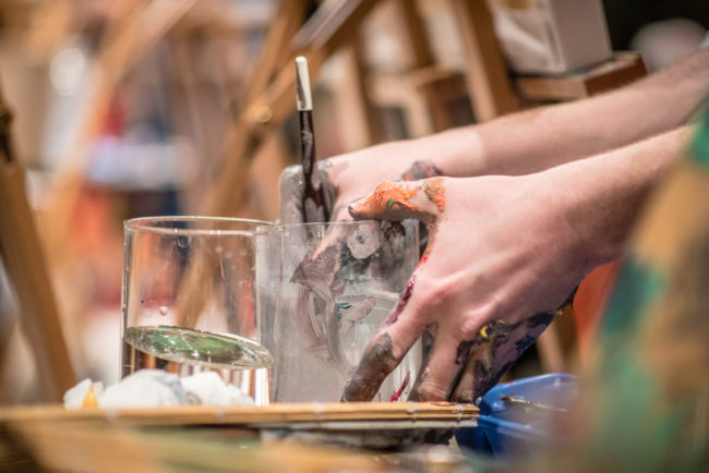 A photo of an artist's hand, mixing paint, at a previous Brush Off.