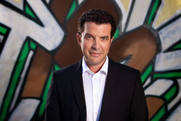 A photo of Canadian comedian, Rick Mercer, in front of a graffiti wall.