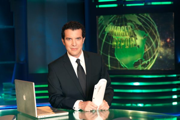 A photo of Rick Mercer sitting at his news desk.