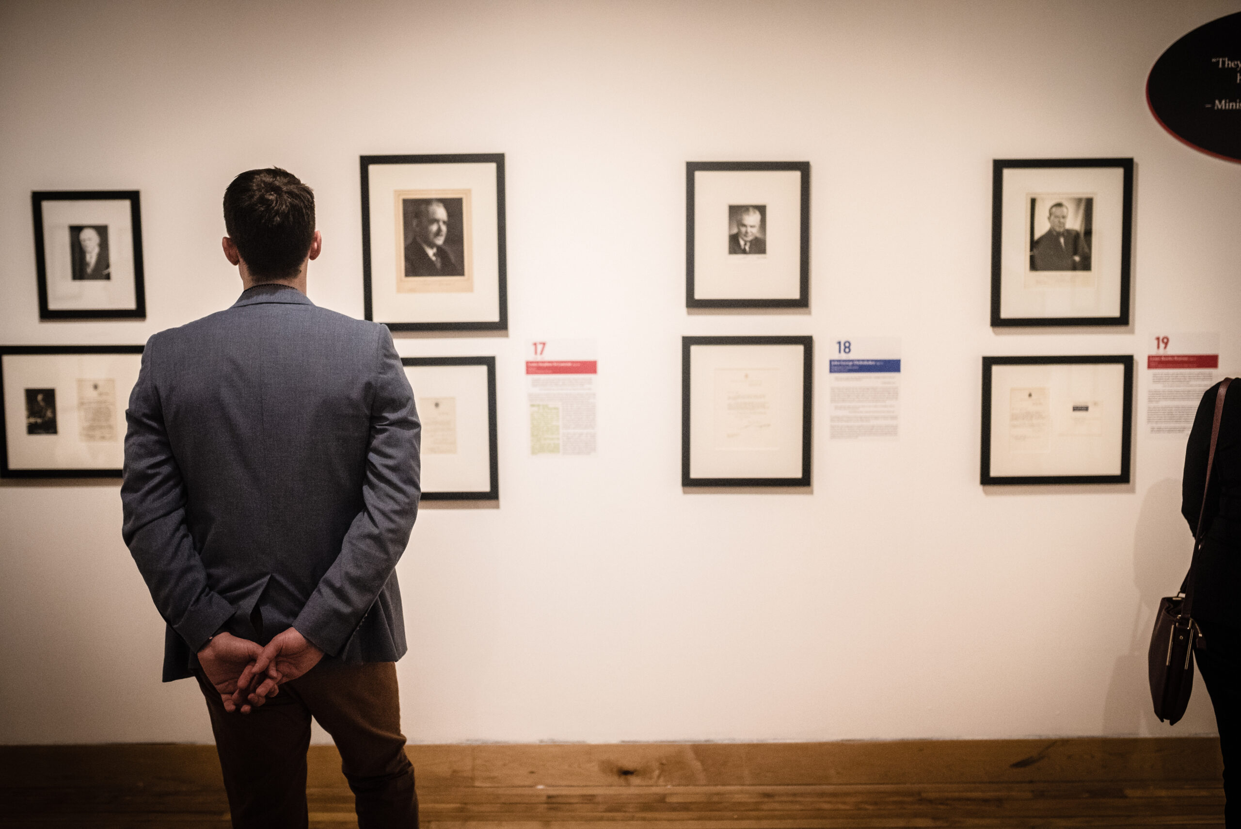 A man looks at artwork on a white wall.
